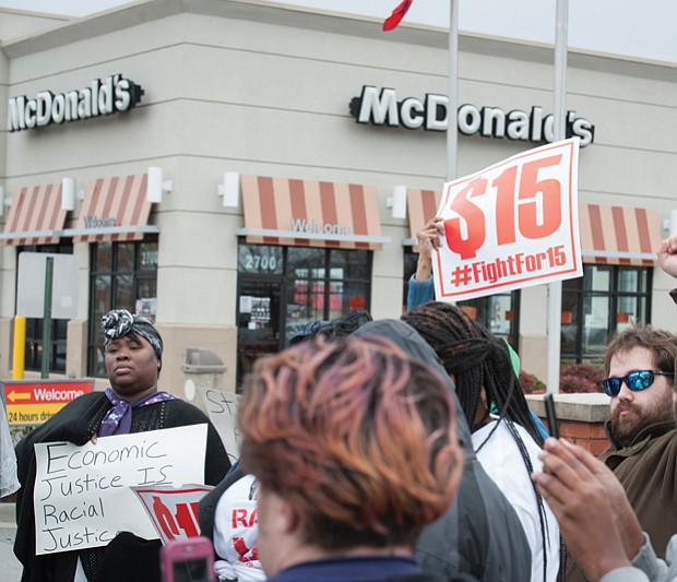 On Monday, protests were held across the nation marking the anniversary of the Memphis strike and calling for higher wages for workers. Bernadette Brown, left, holds a sign outside a Richmond fast food restaurant, while Daniel Henegar, right, and others show their support. The protests were organized by Fight for $15 and the New Poor People's Campaign, which is led by the Rev. William J. Barber II of North Carolina.