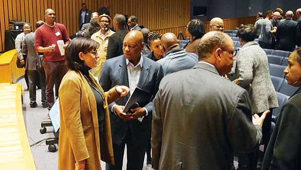 BECMA co-founder Darryl Settles (center) and other attendees conversed after the Feb. 26 forum at the Federal Reserve Bank of Boston.