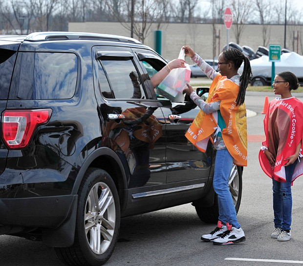 Going all out for Girl Scout cookies //  If there's any question about the power of Girl Scout cookies, look no further. Car loads of customers head through a Girl Scout cookie drive-thru Saturday in the parking lot of Cabela's sporting goods store in Short Pump, where scouts from area troops assisted them with purchases of  their favorite cookie varieties as part of National Girl Scout Cookie Weekend. Above, scouts Dionne Washington, Tyshaunda Jennings and DeRanae Jones of Troop #007 fill a motorist's cookie order