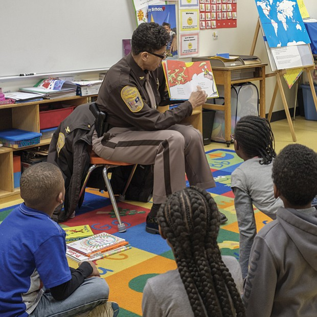 The joy of reading // Adults are spreading the joy of reading to area children. Left, Richmond Sheriff Antionette V. Irving reads to students at Overby-Sheppard Elementary School in North Side on Tuesday