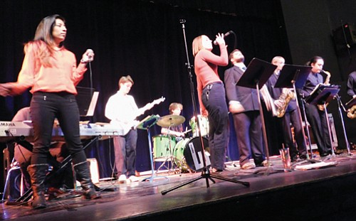 Estefania Tapia (left), one of the music teachers helping keep alive an after-school band program at Jefferson High School, fills in on vocals during a dress rehearsal of the Pacific Northwest Show Band, held recently at the school, drawing students from all over the metro area. Tapia is also director of the Sounds of Jefferson band, created just for Jefferson High students.