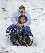 Bridget Mitchell, back, sleds down the Water Tower hill in Chestnut Hill with her daughter, Olivia Mitchell, 9, in Philadelphia on Wednesday, March 7, 2018. The second big storm to hit the Northeast in less than a week brought wet, heavy snow Wednesday to a corner of the country where tens of thousands of people were still waiting for the power to come back on from the first bout of wintry weather. (Michael Bryant/The Philadelphia Inquirer via AP)