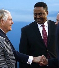 U.S. Secretary of State Rex Tillerson, left, is greeted by Ethiopia Minister of Foreign Affairs, Workneh Gebeyehu, right, and other officials, as he arrives to begin a six-day trip in Africa, after landing at Addis Ababa International Airport, Wednesday, March 7, 2018 in Addis Ababa, Ethiopia. (Jonathan Ernst/Pool via AP)