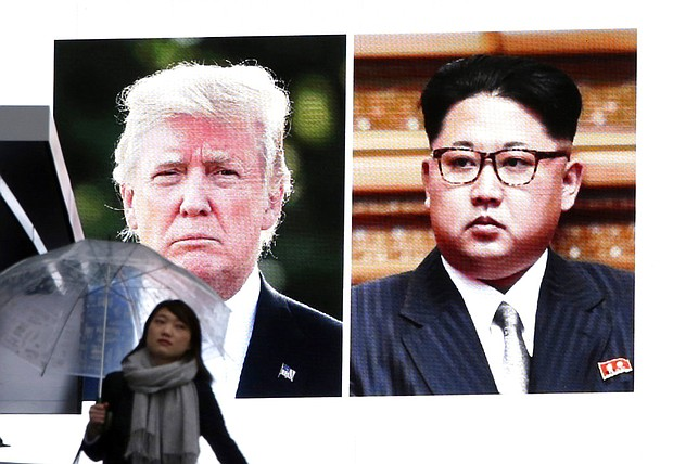 A woman walks by a huge screen showing U.S. President Donald Trump, left, and North Korea's leader Kim Jong Un, in Tokyo, Friday, March 9, 2018. After months of trading insults and threats of nuclear annihilation, Trump agreed to meet with Kim by the end of May to negotiate an end to Pyongyang's nuclear weapons program, South Korean and U.S. officials said Thursday. (AP Photo/Koji Sasahara)