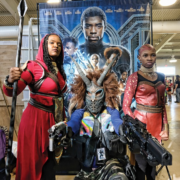"'Black Panther' flair // This trio appears to be straight out of the film ""Black Panther"" as they take part in VA Comicon last Saturday at the Old Dominion Building at Richmond Raceway. Frank Lester, center, is outfitted as the movie's super villain Erik Killmonger. Mia Jones, left, and 12-year-old Cameron Hilliard are dressed as Wakanda warriors, also known as Dora Milaje, the team of female special forces protecting the film's fictional African nation of Wakanda. VA Comicon, where comic books and toys take center stage, was filled with participants who dressed as popular characters."