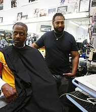 In this Sunday, March 11, 2018, photo, Barber Eric Muhammad, owner of A New You Barbershop measures the blood pressure of customer Marc M. Sims in Inglewood, Calif. Black male customers at dozens of Los Angeles area barbershops reduced one of their biggest health risks through a novel project that paired barbers and pharmacists to test and treat customers. (AP Photo/Damian Dovarganes)