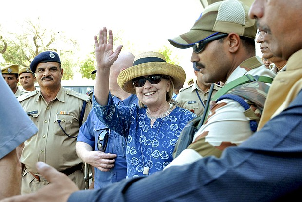 Former U.S. Secretary of State Hillary Clinton, center, waves as she comes out of the Jodhpur airport upon her arrival in Jodhpur, Rajasthan state, India, Tuesday, March 13, 2018. (AP Photo/Sunil Verma)