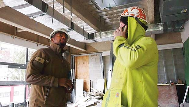 Abdul Barrie and Peter Stewart check duct work in an apartment building under construction in the Bartlett Place development.