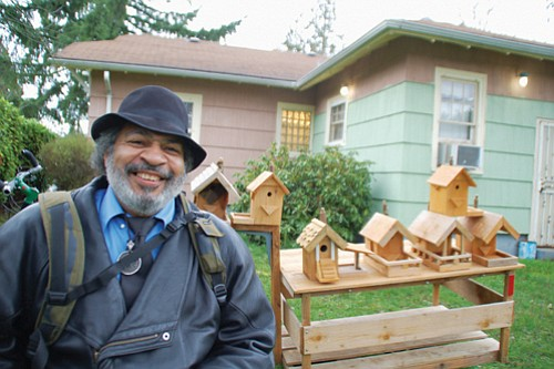 George Mayes poses in front of his bike and birdhouse cart, a device that allows him to haul his unique creations to street corners around town, much to the admiration of passersby.