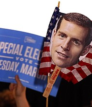 Supporters of Conor Lamb, the Democratic candidate for the March 13 special election in Pennsylvania's 18th Congressional District hold signs during his election night party in Canonsburg, Pa., Wednesday, March 14, 2018. (AP Photo/Gene J. Puskar)