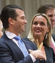 In this Feb. 28, 2017 file photo, Donald Trump Jr. jokingly plays with scissors as his wife Vanessa laughs at the grand opening of the Trump International Hotel and Tower in Vancouver, Canada. A public court record filed Thursday, March 15, 2018 in New York says Vanessa Trump is seeking an uncontested divorce from the president's son. (Jonathan Hayward/The Canadian Press via AP, File)