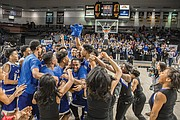 The celebration begins as the John Marshall Justices take the state title last Friday. A perennial powerhouse in the 3A Division, the team finished the season 22-6 after dispatching Western Albemarle High School in the final.