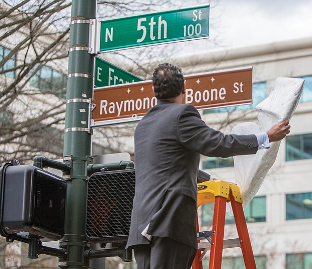 In his honor // Raymond H. Boone Jr. unveils the honorary street sign that pays tribute to his father, the late founder, publisher and editor of the Richmond Free Press. Location: 5th and Franklin streets in front of the Free Press building.