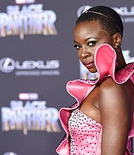 """In this Jan. 29, 2018 file photo, Danai Gurira, a cast member in """"Black Panther,"""" arrives at the premiere of the film at The Dolby Theatre in Los Angeles. Featuring a predominantly black cast, the film that is an ode to Africa - with costuming and sets heavily inspired by African cultures - moved many viewers, including cast members themselves, to dress in African-themed garments for their viewing the film. (Photo by Chris Pizzello/Invision/AP, File)"""