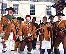 Members of the Lexington Minuteman, a group of Revolutionary War reenactors, gather in front of the Dillaway Thomas House, where Gen. Washington's army was encamped during the siege of Boston.