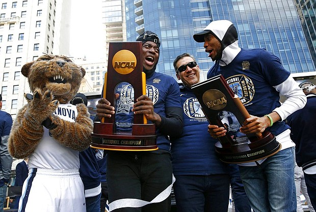 Villanova forward Eric Paschall, second from left, head coach Jay Wright and guard Mikal Bridges celebrate during a rally following a parade for the team's NCAA college basketball championship, Thursday, April 5, 2018, in Philadelphia. Villanova defeated Michigan on Monday for the NCAA men's basketball title. (AP Photo/Patrick Semansky)