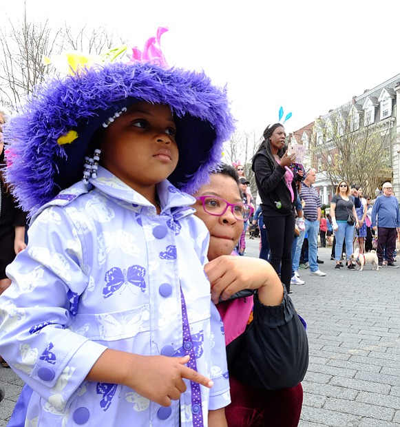 Audrey Ross, 4, pauses with her mother, Tarah Westont, to watch one of the performances at Easter on Parade.