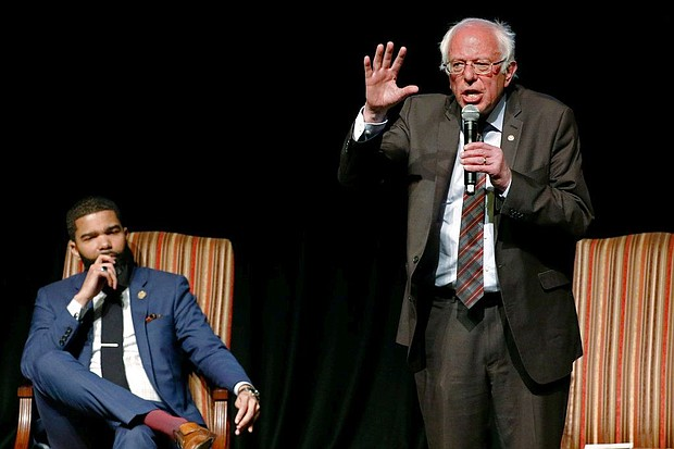 In this April 4, 2018 photo, Jackson Mayor Chokwe Antar Lumumba, left, listens as Sen. Bernie Sanders, I-Vt., answers a question during a town hall meeting examining economic justice 50 years after the assassination of Dr. Martin Luther King Jr., in Jackson, Miss. (AP Photo/Rogelio V. Solis)