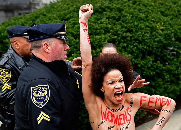 The topless protester who leaped over a barricade and ran toward Bill Cosby at the start of his sexual assault ...