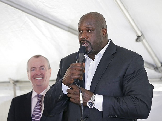 """New Jersey Governor Phil Murphy, left, watches as Newark-native Shaquille O'Neal speaks during an event in Newark, N.J., Tuesday, April 10, 2018. Politicians and other guests were participating in a symbolic """"topping-off"""" ceremony for a 23-story building in downtown Newark. (AP Photo/Seth Wenig)"""
