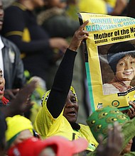 Mourners gather at the Orlando Stadium for the funeral of anti-apartheid icon Winnie Madikizela-Mandela, portrait on placard, in Soweto, South Africa, Saturday, April 14, 2018. Madikizela-Mandela died on April 2 at the age of 81. (AP Photo/Themba Hadebe)