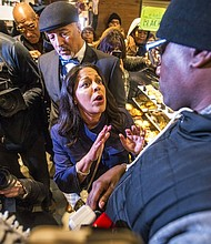 Camille Hymes, center, regional vice president of Mid-Atlantic operations at Starbucks Coffee Company, speaks with Asa Khalif, of Black Lives Matter, right, after protesters entered the coffee shop, Sunday, April 15, 2018, demanding the firing of the manager who called police resulting in the arrest of two black men. (Mark Bryant/The Philadelphia Inquirer via AP)