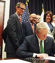 Gov. Charlie Baker signs into law criminal justice reforms that include the elimination of mandatory minimum sentences for some non-violent drug offenses and reforms to the state's CORI laws.