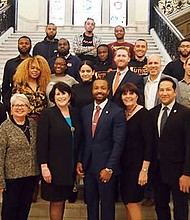 Legislators and criminal justice reform activists gather at the Grand Staircase at the State House to mark the signing of a criminal justice reform bill into law.