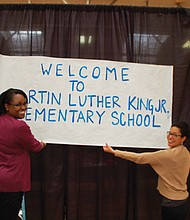 Yolanda Coleman, assistant principal at Martin Luther King School and Lisa Jarrett, a King Museum of Contemporary Art and Portland State University professor, raise a 50 year old poster that was used to rename the school 50 years ago.