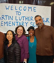 Supporters pose in front of the first sign, created by students in 1968, unveiling Martin Luther King Jr. as the new name for the former Highland  School, during a 50th anniversary community celebration on Friday night honoring the school's legacy. Shei'Meka Owens, King Parent Teacher Association president, and the daughter of Ronda Chiles, who as a sixth grade student at King 50 years ago helped lobby for the name change is pictured (second from right). Owens now has two daughters that attend King. The others pictured are King PTA leaders Paul Manson, May Wang, Megan Newell-Ching and Kenny Butler.