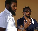 In this Wednesday, April 18, 2018 photo, Rashon Nelson, left, listens as and Donte Robinson, right, addresses a reporter's question during an interview with The Associated Press in Philadelphia. Their arrests at a local Starbucks quickly became a viral video and galvanized people around the country who saw the incident as modern-day racism. (AP Photo/Jacqueline Larma)