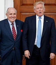 In this Nov. 20, 2016, file photo, then-President-elect Donald Trump, right, and former New York Mayor Rudy Giuliani pose for photographs as Giuliani arrives at the Trump National Golf Club Bedminster clubhouse in Bedminster, N.J. (AP Photo/Carolyn Kaster, File)