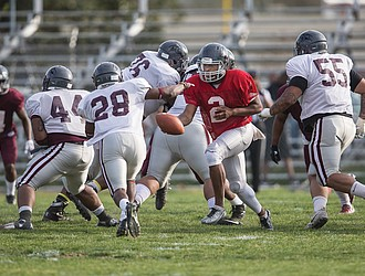 Quarterback Eric Caldwell hands off the ball to running back Coby Williams during Virginia Union University's intrasquad game last Saturday at Hovey Field. Caldwell threw two touchdown passes during the game.