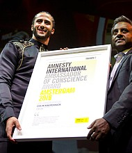 Former NFL quarterback and social justice activist Colin Kaepernick receives the Amnesty International Ambassador of Conscience Award for 2018 from Amnesty International Secretary General Salil Shetty, right, in Amsterdam, Saturday April 21, 2018. (AP Photo/Peter Dejong)
