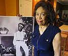 In this Wednesday, April 18, 2018 photo, Josephine Bolling McCall poses with a photo of her father, lynching victim Elmore Bolling, at her home in Montgomery, Ala. Bolling is among thousands of lynching victims remembered at the new National Memorial for Peace and Justice, erected with donations by the Alabama-based Equal Justice Initiative. (AP Photo/Jay Reeves)