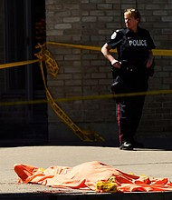 A police officer stands over a covered body in Toronto after a van mounted a sidewalk crashing into pedestrians on Monday, April 23, 2018. (Nathan Denette/The Canadian Press via AP)