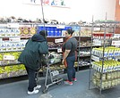 A volunteer helps a client at the Bed-Stuy Campaign Against Hunger food pantry