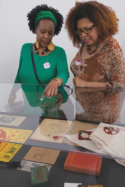 "Sonja Holt, left, and Dawn Howard peruse a display in the exhibition ""Storm in the Time of Shelter"" by artist Paul"