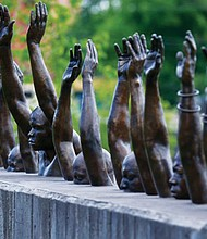 """A bronze statue called """"Raise Up"""" is part of the display at the new National Memorial for Peace and Justice in Montgomery, Ala. a new memorial to honor thousands of people killed in lynchings.  (AP photo)"""