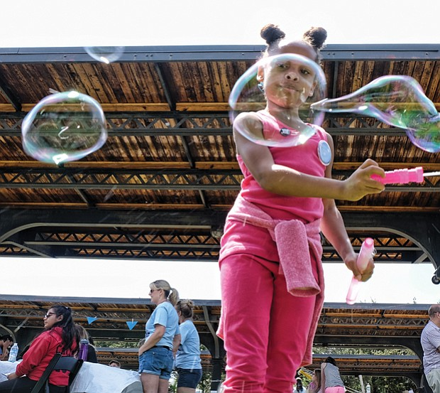 Jo-lynn Carter creates big bubbles, below, in the kids' activity zone //