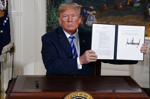 President Donald Trump shows a signed Presidential Memorandum after delivering a statement on the Iran nuclear deal from the Diplomatic Reception Room of the White House, Tuesday, May 8, 2018, in Washington. (AP Photo/Evan Vucci)