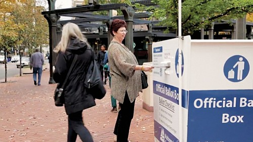 A voter casts her ballot at one of Multnomah County's eight 24-hour election drop boxes.  Election officials recommend dropping off vote-by-mail ballots at official drop off sites like these if you can't get them into the mail by Thursday in order for it to have time to be delivered by the voting deadline of Tuesday, May 15 at 8 p.m.
