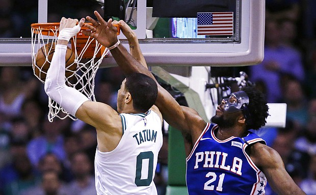Boston Celtics forward Jayson Tatum (0) dunks after a drive past Philadelphia 76ers center Joel Embiid (21) during the second half of Game 5 in Boston, Wednesday, May 9, 2018. Tatum scored 25 points as the Celtics defeated the 76ers 114-112 to advance. (AP Photo/Charles Krupa)