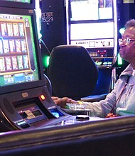 This April 20, 2018 photo shows a woman playing slot machines at Resorts Casino Hotel in Atlantic City, N.J. (AP Photo/Wayne Parry)