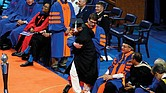 University of Florida student Oliver Telusma is manhandled by a college usher after dancing with joy in his walk across the stage to receive his degree. University President Kent Fuchs, seated at Mr. Telusma's right, issued apologies a day later.
