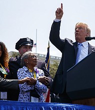 President Donald Trump points to the sky as he talks to the family of slain New York Police Detective Miosotis Familia, during the 37th annual National Peace Officers Memorial Service on Capitol Hill, Tuesday, May 15, 2018, in Washington. (AP Photo/Evan Vucci)