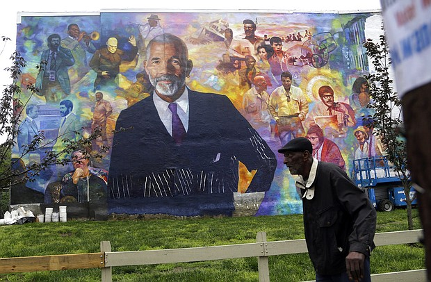 A pedestrian walks past a mural of journalist Ed Bradley, Wednesday, May 16, 2018 in Philadelphia. The mural, by artist Ernel Martinez, is in the Belmont neighborhood of west Philadelphia where Bradley grew up. (AP Photo/Jacqueline Larma)