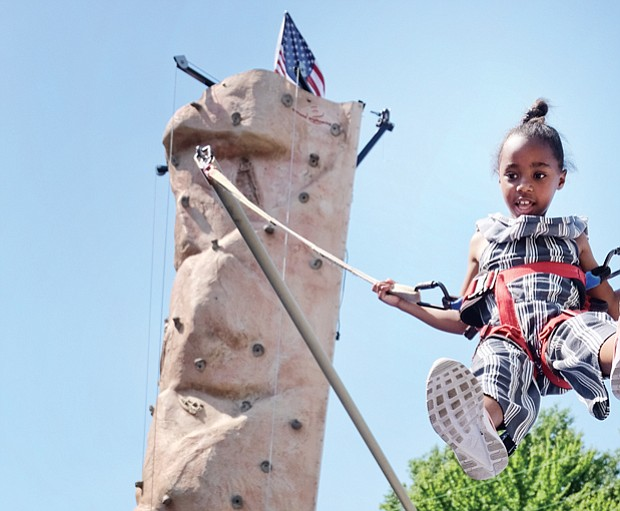 Fun for a cause // Ava Miller flies high on a bungee bouncer at last Saturday's Strawberry Street Festival in The Fan. It was the 39th year for the event sponsored by the William H. Fox Elementary School PTA to benefit the public school in Richmond.