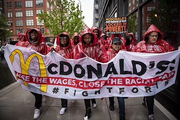 "Carrying signs reading ""Black Workers Matter, McDonald's"" and chanting ""We Believe That We Will Win,"" workers in McDonald's uniforms were ..."