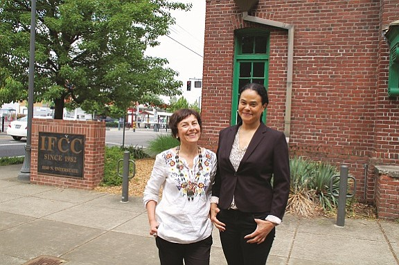 """Laura Lo Forti (left) and Damaris Webb, co-organizers of the Vanport Mosaic Festival, pose outside the Interstate Firehouse Cultural Center on North Interstate Avenue, showcasing one of the primary event venues for the annual celebration taking place this long Memorial Day weekend on the 70th anniversary of the Vanport Flood. The IFCC will host several exhibitions, like Vanport: The Surge of Social Change; Anywhere but Here: The History of Housing and Discrimination in Oregon; and Our City, Our Voice: Excavating Portland's History through Art. A new play about displacement in Portland, """"Left Hook,"""" will also make its world premiere at the IFCC on Thursday."""